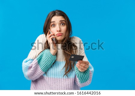 Gloomy and indecisive confused cute girl calling bank service cant understand where all money go during winter holidays shopping season, talking on phone, holding credit card, blue background