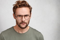 Gloomy bearded man with serious grumpy expression, looks strict, being angry with someone, has irritated or annoyed expression. Unhappy skeptical young male makes grimace over white studio wall