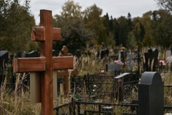 Gloomy Christian cemetery. Burial place of people. Orthodox cemetery grave cross. Tombstones and monuments.