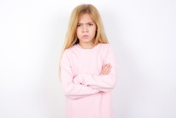 Gloomy dissatisfied beautiful caucasian little girl wearing pink sweater looks with miserable expression at camera from under forehead, makes unhappy grimace