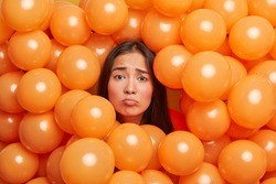 Gloomy dissatisfied upset Asian woman being not ready to celebrate poses around party balloons expresses negative emotions comes on friends birthday. Spoiled holiday concept. Festive event or occasion