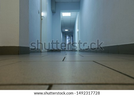 Gloomy empty office corridor with a door at the end. Blue walls, tiled floor and cold blue light lamps. Low angle view