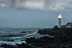Gloomy gloomy photo of a luminous lighthouse on a rocky shore. Famous lighthouse. Portland. USA. Maine