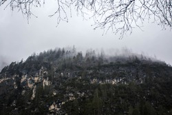 Gloomy landscape of rainy foggy mountains in North Italy. Fog in the dark forest in the mountains.