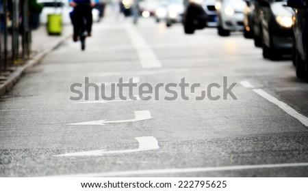 Gloomy road with arrows, bicylist distant