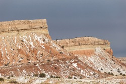 Gloomy sky behind sharp rock mountain formations with snow streaks in rural New Mexico