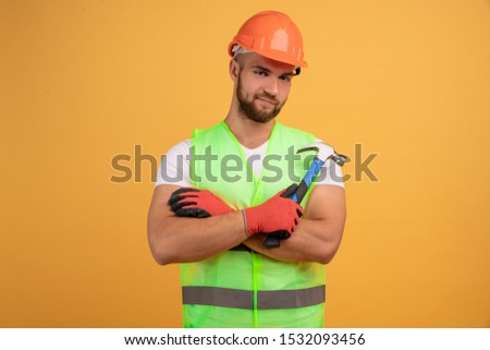 Gloomy unhappy male repairer has sad tired look, keeps hands crossed, holds hammer in hand, fatigue after repairing and manual work, wears special uniform. Handcrafting, hammering, building.