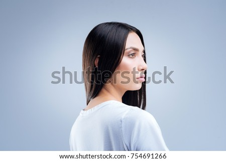 Gloomy woman. Serious concentrated young woman standing against the blue background and looking into the distance while preparing for the unpleasant conversation with her boyfriend