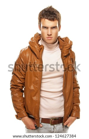 Gloomy young man in brown jacket, it is isolated on black background.