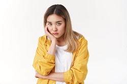 Gloomy young sad asian blond girl sighing upset stoop look from under forehead lonely unhappy lean palm bored feel regret sadness moody expression standing white background pessimistic