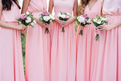 Glorious bridesmaids in pink dresses  holding beautiful flowers