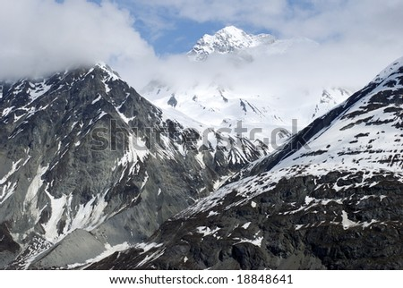 Glorious mountains covered by clouds and snow in Glacier Bay national park, Alaska.