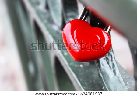 Gloss red Valentines Day Heart shape wedding lock hangs on metal fence bridge of lovers. Saint Valentine's Day card on blurred background. Symbol of love, romance, relationship, happy family concept