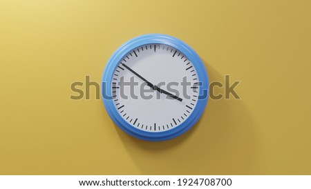 Glossy blue clock on a orange wall at fifty-one past three. Time is 03:51 or 15:51 Foto stock ©