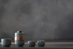 Glossy reflective countertop with nice ceramic blue teapot set, three small cups, brewing tea for guests, healthy and organic drink, grey wall in blurred background with copy space for text