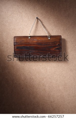 Glossy wood sign hung on background.