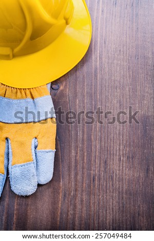 glove and helmet on vintage wooden board with copyspace construction concept