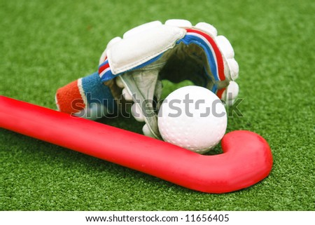 Glove with a red stick on green grass