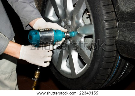 Gloved car mechanic hands removing wheel nuts to check brakes.