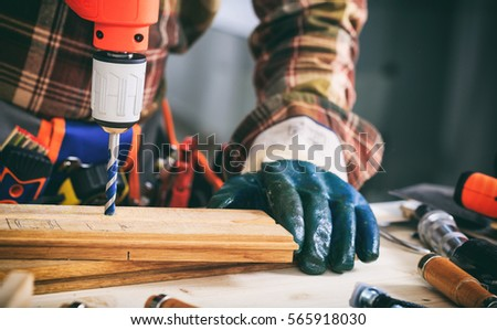 Gloved carpenter working with an electric drill on a wooden plank