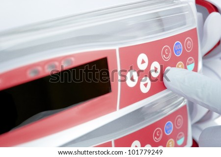 gloved finger, pressing the button of the modern device. photo