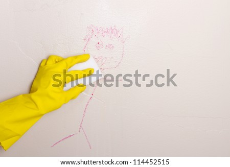 Gloved hand, cleaning crayon off wall with magic eraser