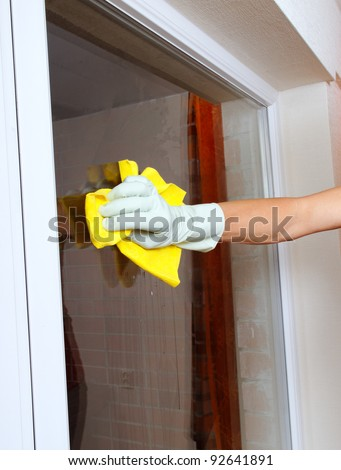 Gloved hand cleaning window.