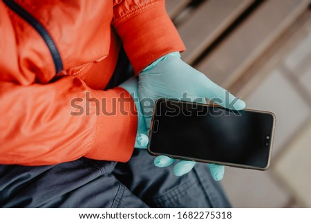 Gloved hand holding a smartphone