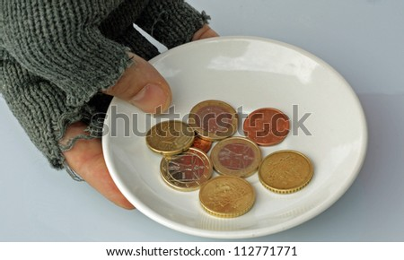 gloved hand of a poor and saucer with a few coins