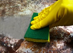gloved hand scrubbing a dirty metal surface