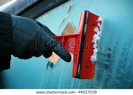 Gloved hand using an ice scraper on iced glass