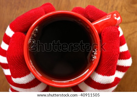 Gloved hands holding mug filled with hot beverage.  Macro with shallow dof.  Copy space inside mug.