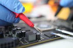 Gloved master holds probe over microcircuit. Repair and maintenance of e microcircuits concept