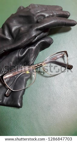 Gloves. Leather gloves and glasses on leather background. Vintage photo