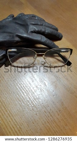 Gloves. Leather gloves and glasses on wood background. Vintage photo