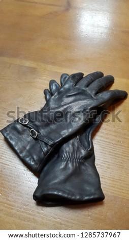 Gloves. Leather gloves. Black leather gloves on dark wood
