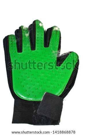 Gloves stroking green dog hairs on a white background