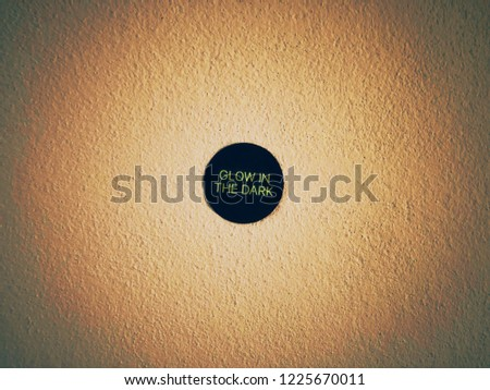 Glow in the dark sticker on sepia tone glowing light filter on wall. Minimal style. Copy space. #1225670011