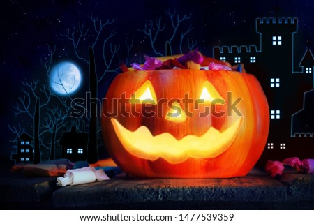 Glow light pumpkin lantern which have smile face decorate with candy decorate on wood table with background dark village and moon on night sky. #1477539359