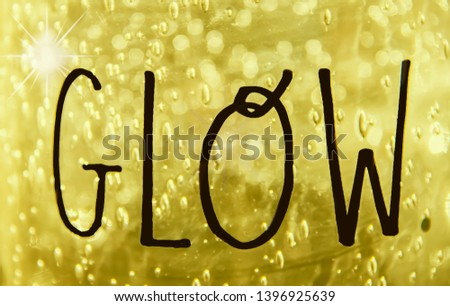 GLOW - The word glow written in freehand on golden bokeh textured background with sparkle