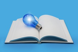 Glowing Blue light bulb on open blank notebook on blue background , education with ideation , intellectual and wisdom concept