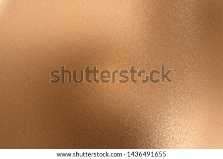 Glowing bronze metallic wall with scratched surface, abstract texture background