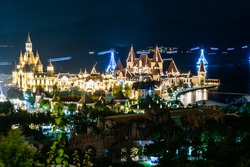 Glowing buildings in amusement park at night with funicular over sea