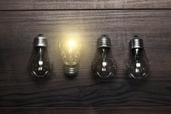 glowing bulb uniqueness concept on brown wooden background