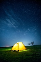 Glowing camping tent in the night mountains under a starry sky