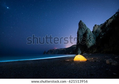 Glowing camping tent on a beautiful sea shore with rocks at night under a starry sky #621513956