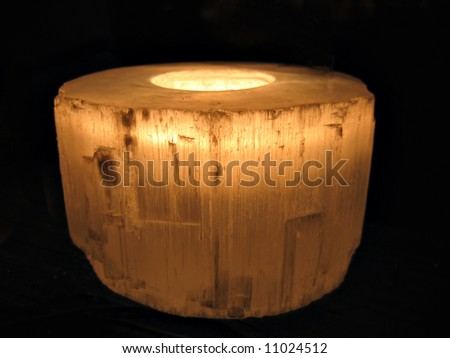 Glowing candle in a transparent holder with black background