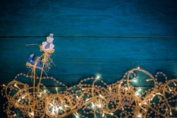Glowing Christmas lights, silver beads and decorations deer and snowman on sticks on blue wooden background. Top view with copy space