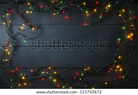 Glowing Christmas tree garland in the form of a frame on a blue wooden background