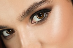 Glowing. Close up of young female fashion model's face with eye smoky make up. Beautiful caucasian woman with trendy make-up and well-kept skin. Style and beauty concept. Eyes looking in camera.